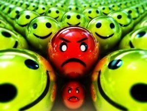 Anger concept - one red grumpy ball in the middle of happy green balls