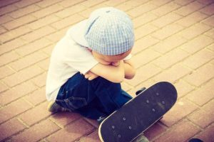 sad boy alone with a skateboard