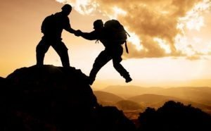 man helping another man up a mountain